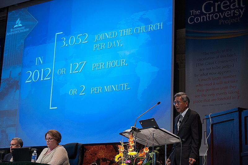 """Adventistsamfundets generalsekreterare G. T. Ng ursäktar sig för tryckfelet i medlemsrapporten. Den har producerats i Sydamerika och därför står det """"3.062"""" istället för """"3,062"""" [på svenska skulle det ha stått """"3 062""""]. Foto: Ansel Oliver/ANN"""